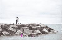 Chica y chicos de lejos abrazados en las rocas del mar